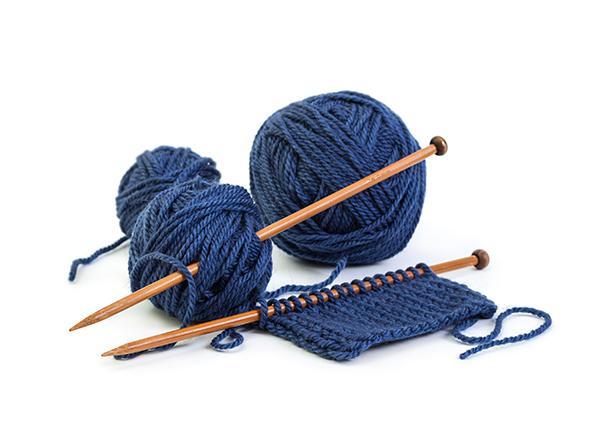 image of blue ball of yarn and knitting needles