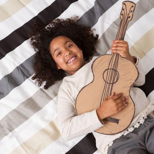 image of girl playing cardboard guitar