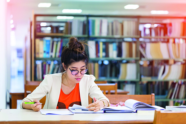 image of girl writing in library