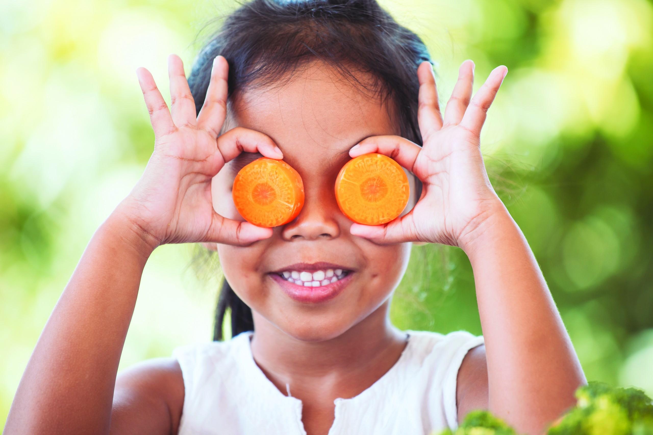 cute girl covering eyes with fruit like binoculars